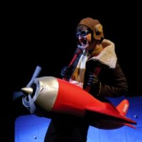 The boy flies his plane to the moon in The Way Back Home on stage
