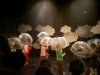 children on stage with umbrellas